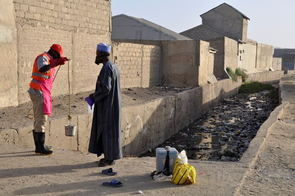 Environmental surveillance officers in Nigeria check a water source for evidence of polio.