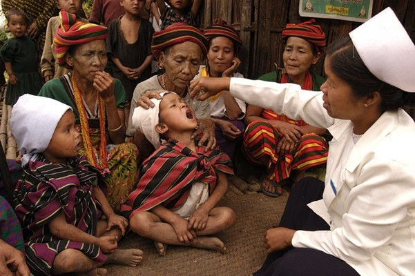 Children and elderly women watch community health worker Daw San Yee (right) vaccinate a child against polio in Kan Thar Yone Village in the western state of Chin in Myanmar.