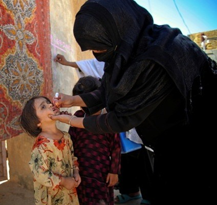 A woman health worker in Baluchistan, Pakistan, gives a child the oral polio vaccine.