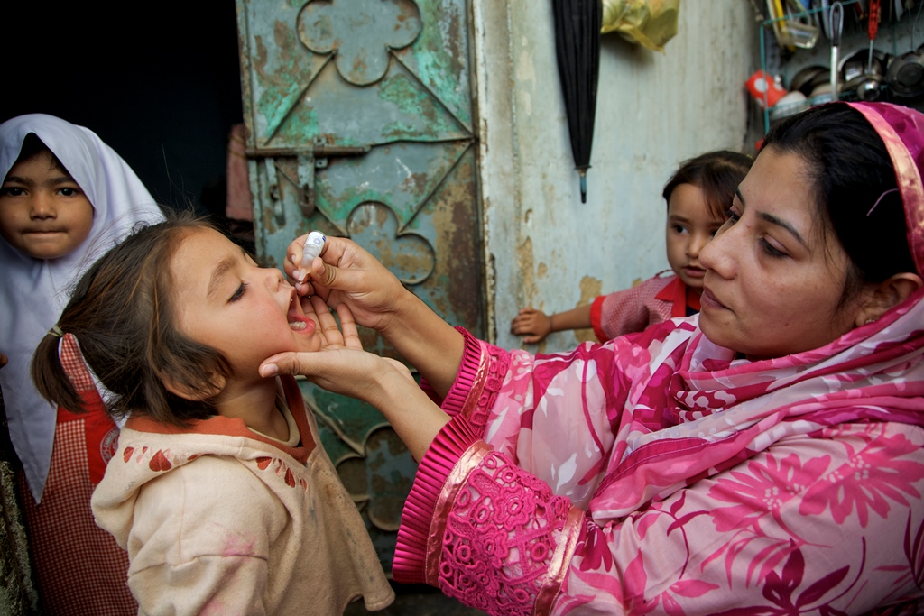 A health worker vaccinates a child against polio outside her home during Polio – National Immunisation Day (NID, while her sisters watching in Sherpow in Landhi town, Karachi Pakistan.