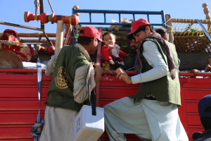 Two vaccinators climb onto a truck to deliver polio vaccines to a family travelling across Torkham border into Afghanistan. © WHO/S. Ramo