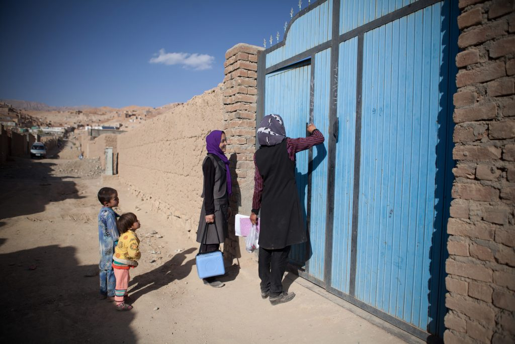 After visiting a household, Tahera and her colleague mark the door to record the number of children that have been vaccinated or missed. Photo: WHO/R.Akbar