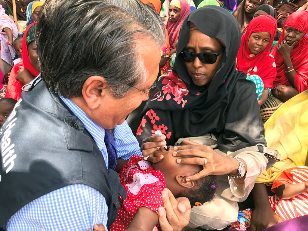 In Somalia, a Member State of the Organization of Islamic Cooperation, Minister of Health Dr Fawziya Abikar Nor (right), and Dr Ghulam Popal, WHO Representative for Somalia, vaccinate a child against polio. ©WHO / A.Wolasmal