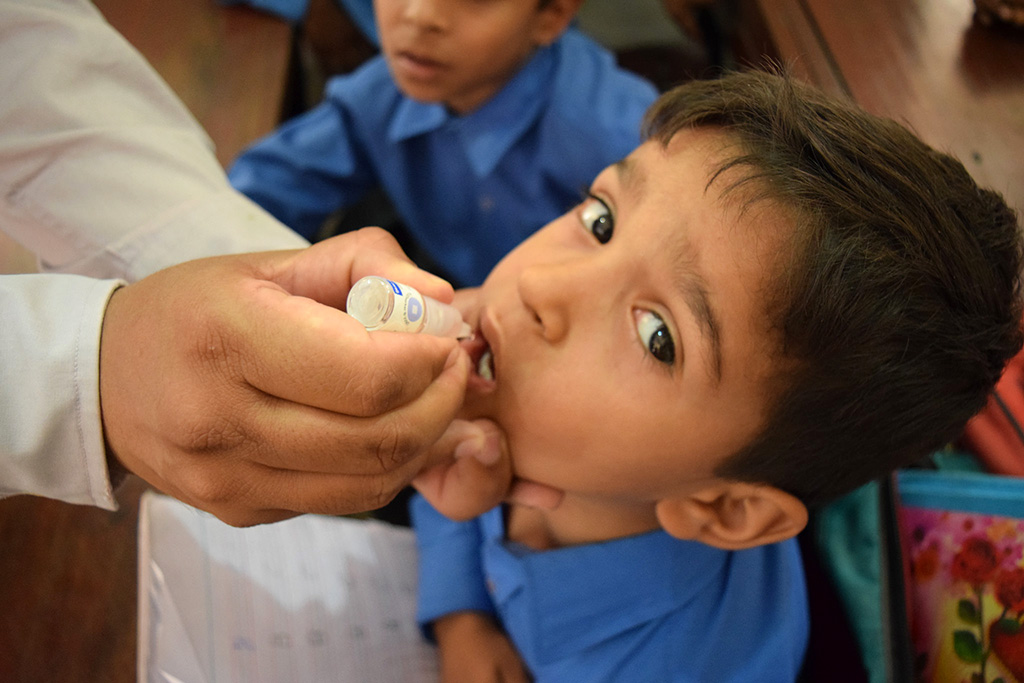 A boy getting vaccinated against polio in school during a campaign in Lahore, Pakistan in May 2018. © WHO EMRO / Anam Khan