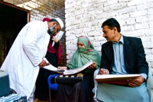 EPI Vaccinators and CBVs refer to Routine Immunization Register during visit to an urban slum, Sikandar Town Peshawar. ©UNICEF/ Kyinat Motla
