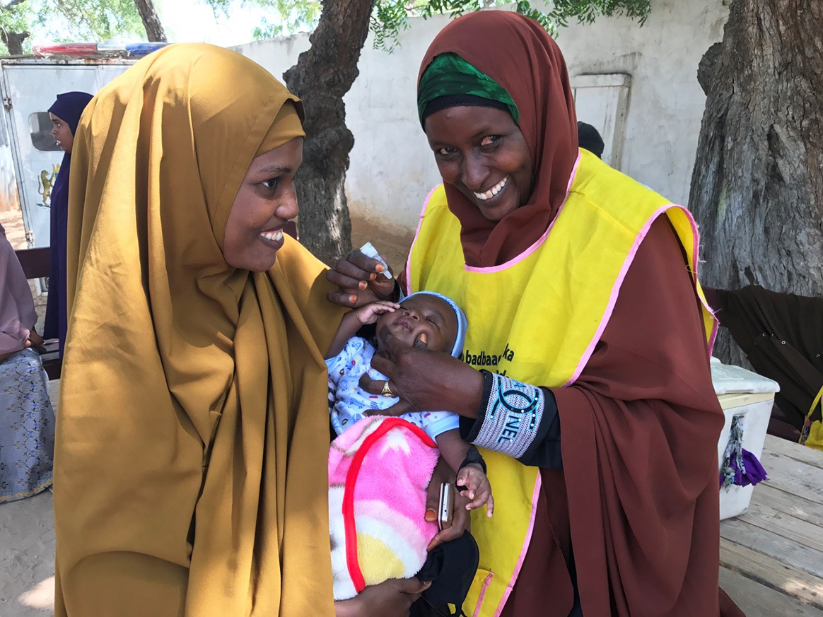 Bella smiles as she vaccinates a small baby against polio – one of hundreds of children she will protect over the course of a campaign. © WHO Somalia