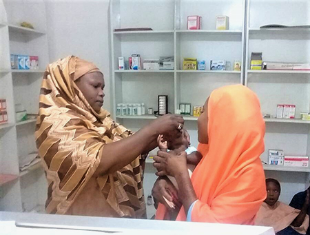 Halima administers the oral polio vaccine to a child at a pharmacy where she works as a polio surveillance focal point. © WHO Nigeria