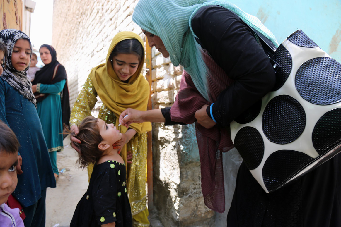 A female vaccinator administers polio vaccine during a campaign in Kabul, Afghanistan. © WHO/J Swan
