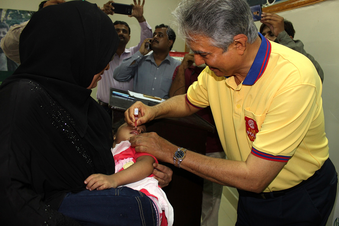 The Rotary National Chair gives a child oral polio vaccine, protecting her against the virus for life. © WHO Pakistan