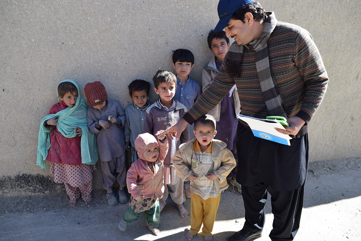 Dr Taj Muhammad interacts with children during a polio immunization campaign in Sadar Union Council, Killa Saifullah district, Balochistan, Pakistan. © S. Mughal/WHO Pakistan
