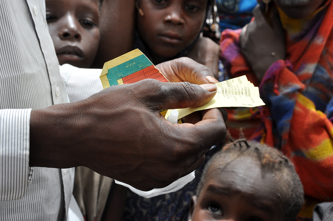 A UNICEF health worker inspects the baby's vaccination card. © WHO/D. Levison