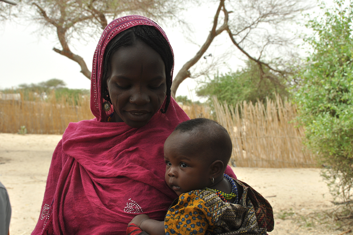 A mother and her child wait for routine immunization services in Mélea camp for internally displaced persons. © WHO/D. Levison