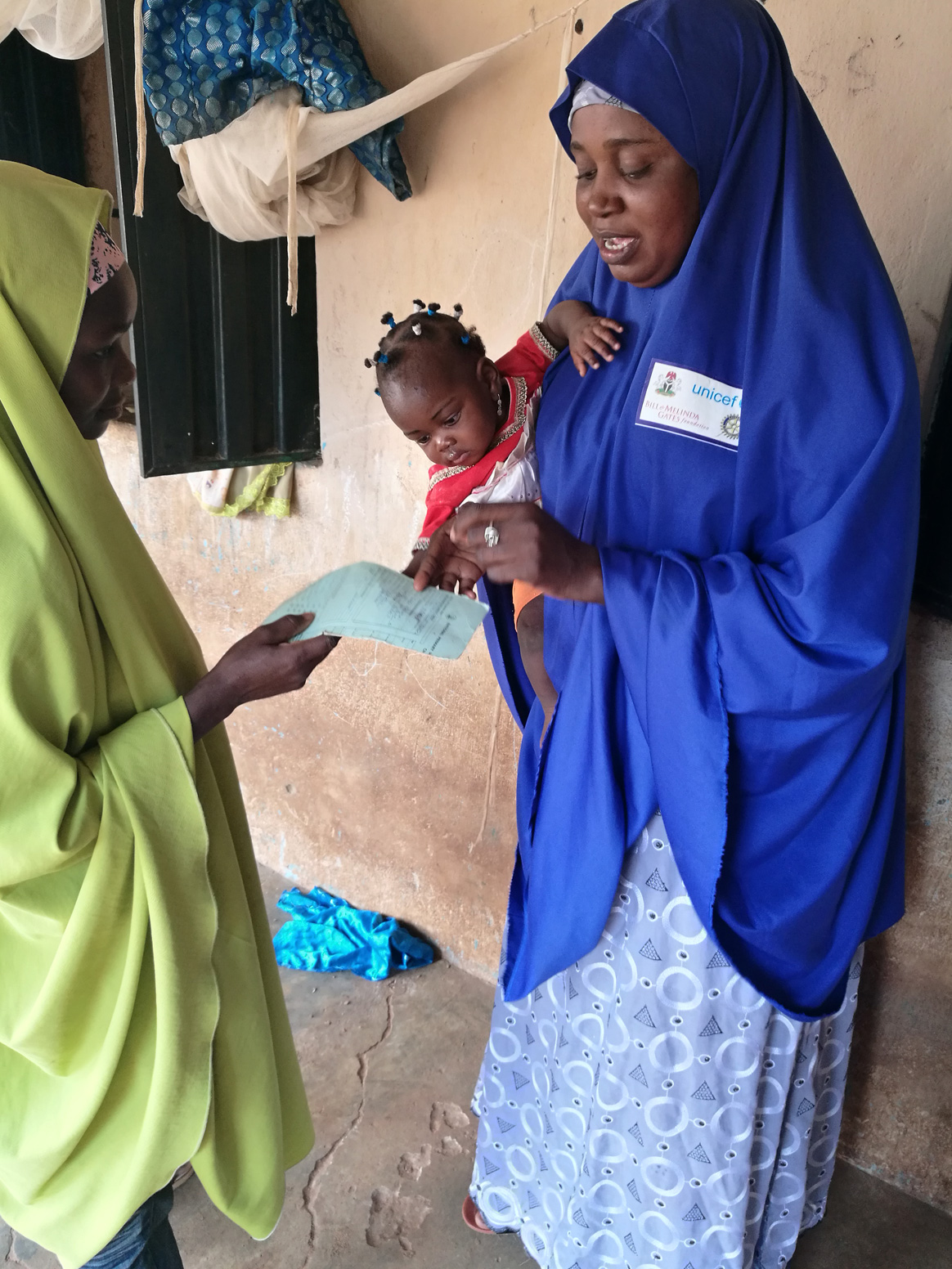 Hauwa inspects a baby's vaccination card. By building up trusting relationships with her community, her health advice gains credibility. © UNICEF/Nigeria