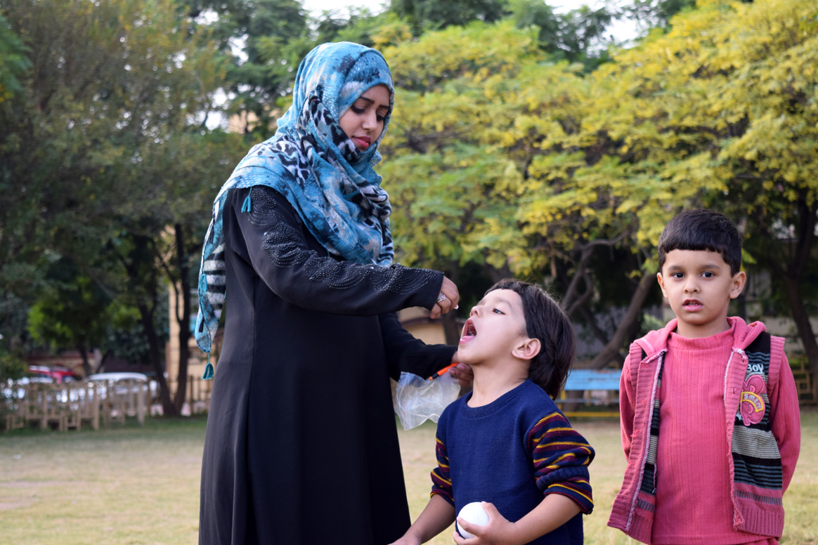 Hafiza administering polio vaccine to a young child in Islamabad, Pakistan. © WHO Pakistan/S.Kashif