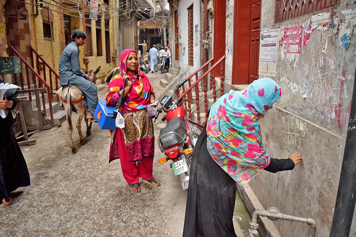 A polio team doing marking a door in Ravi Town, Lahore during NID III © WHO/A.Khan