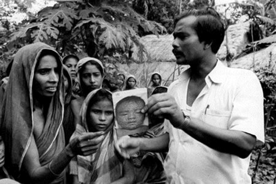 A health worker shows a smallpox recognition card to women in a village, Bangladesh, 1975. © WHO