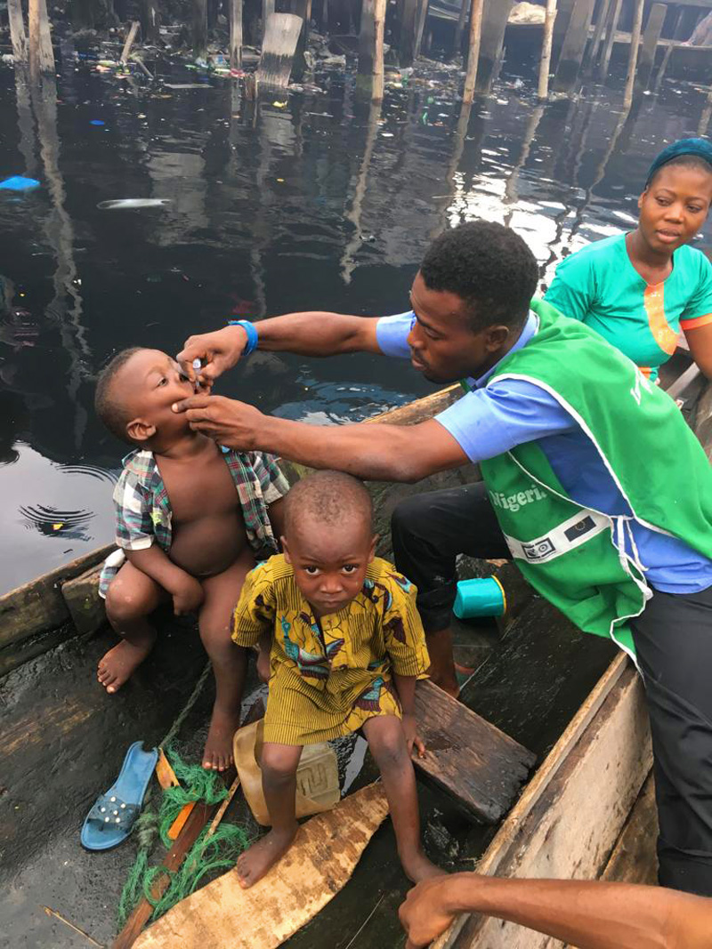 Immunizing a small boy on a canoe as they ferry across their village, Makoko. © UNICEF/Peter Idowu