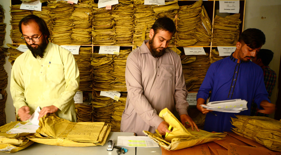(L-R): Jan Sayyed, Ali Raza and Muhammad Bilal Wasi Jan sifting through thousands of forms from across the country. © Mobeen Ansari
