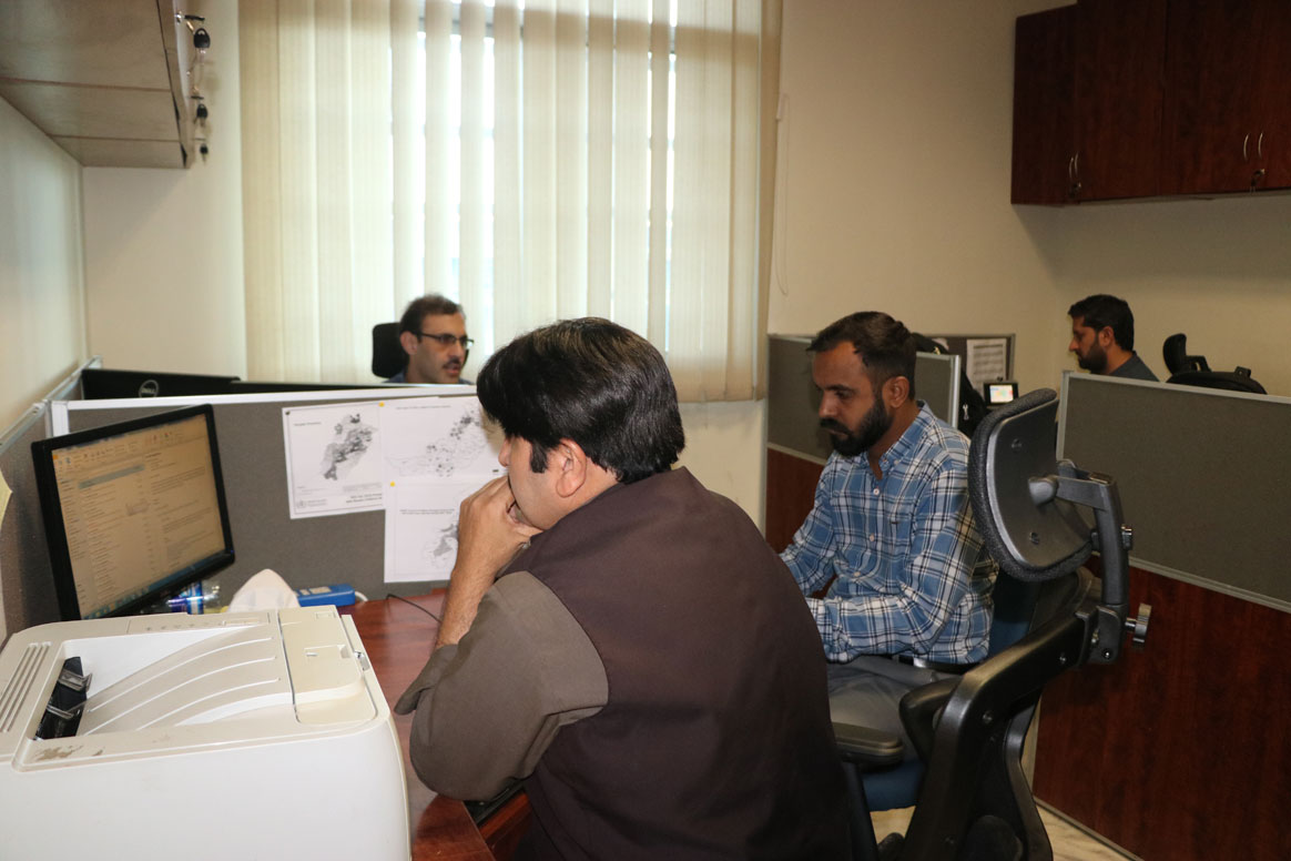 Data experts poring over the latest numbers on the Integrated Disease Information Management System (IDIMS). © Sadaf Kashif