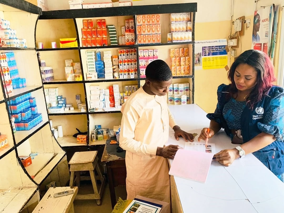 Dr Alhassan explains the key signs of acute flaccid paralysis to a pharmacist in Borno State. ©WHO/Nigeria