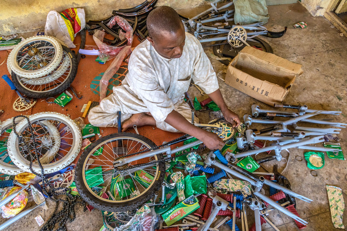 Isiaku Musa Maaji, a polio survivor himself, makes a living by building tricycles for people with mobility impairments. © Rotary International